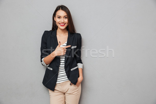 Smiling asian business woman with arm in pocket pointing away Stock photo © deandrobot