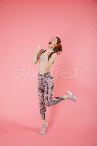 Full length image of Screaming happy sportswoman jumping and rejoices Stock photo © deandrobot