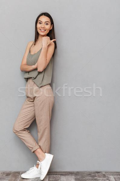 Teljes alakos portré mosolyog ázsiai nő mutat Stock fotó © deandrobot
