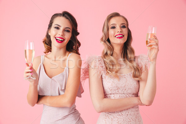 Two Happy elegant women in dresses posing together with champagne Stock photo © deandrobot