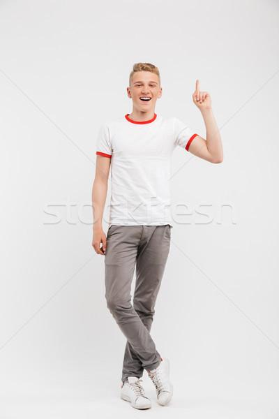 Teljes alakos portré mosolyog tizenéves fiú mutat felfelé Stock fotó © deandrobot