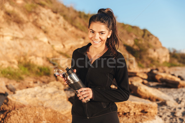 Smiling young sportswoman standing at the seaside Stock photo © deandrobot