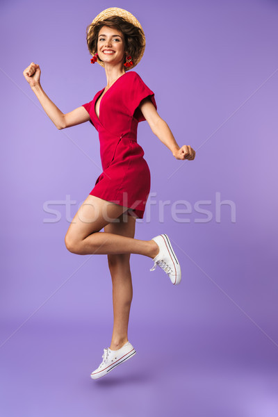 Full length portrait of a cheerful young woman in hat Stock photo © deandrobot