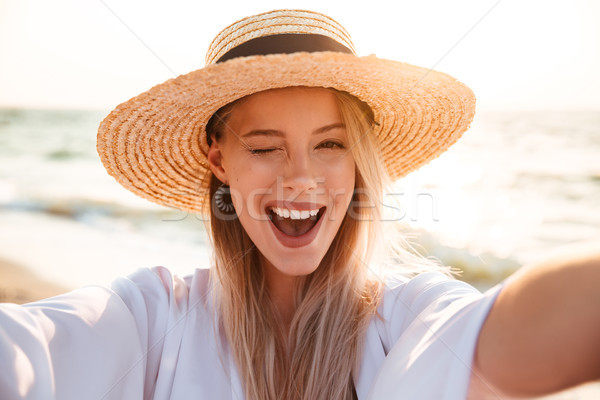Portrait of lovely pleased blonde woman 20s in summer straw hat  Stock photo © deandrobot