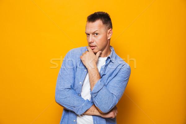 Portré töprengő középkorú férfi néz kamera izolált Stock fotó © deandrobot