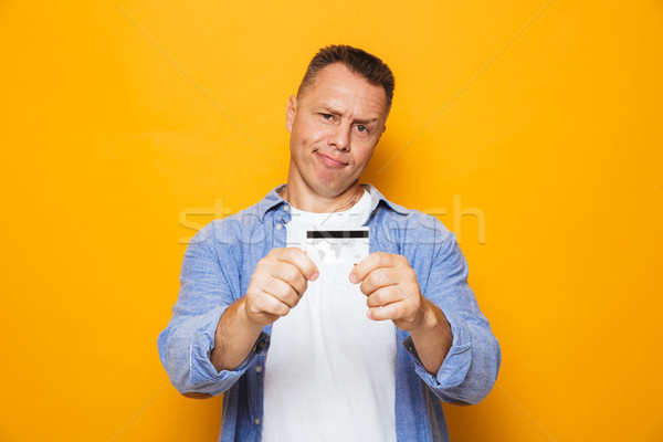 Portrait of an upset middle aged man showing credit card Stock photo © deandrobot