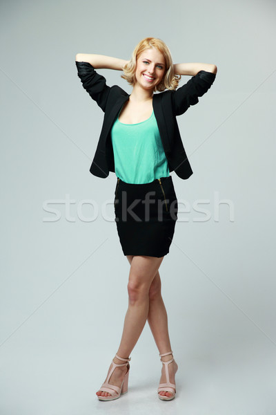 Full length portrait of a young businesswoman on gray background Stock photo © deandrobot