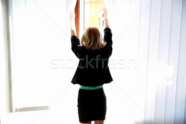 Back view portrait of a young woman looking at window Stock photo © deandrobot