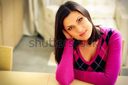 Young pensive woman sitting at the table at home Stock photo © deandrobot