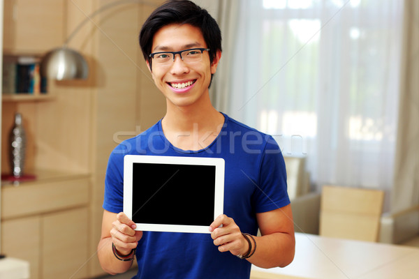 Stock photo: Young happy asian man showing tablet computer screen at home