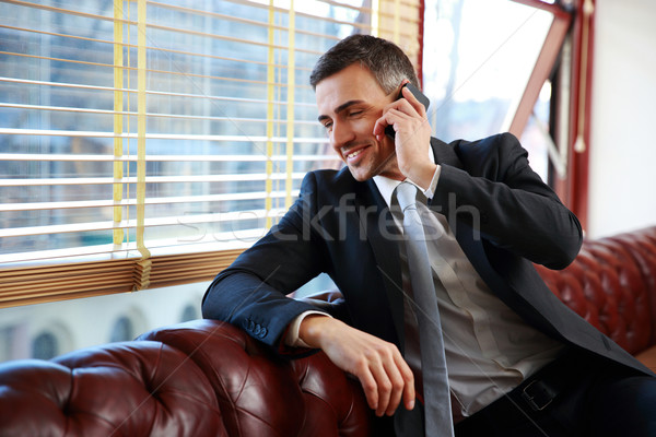 Happy businessman talking on the phone and looking in window at office Stock photo © deandrobot
