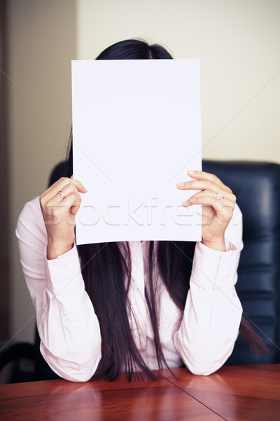 The new worker holds the white blank paper in front of her face Stock photo © deandrobot