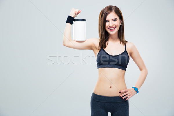 Smiling sporty woman with jar of protein Stock photo © deandrobot