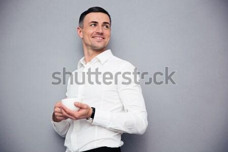 улыбаясь бизнесмен Постоянный оружия сложенный серый Сток-фото © deandrobot