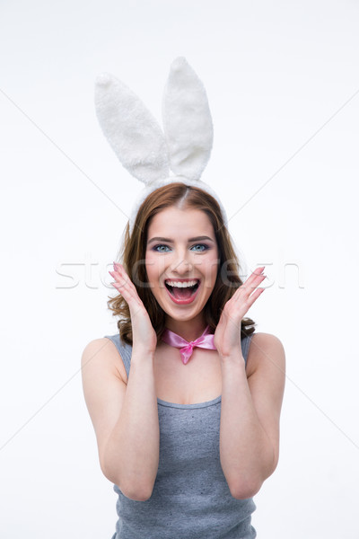 Laughing young woman in rabbit ears over gray background Stock photo © deandrobot