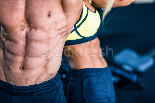 Muscular man's and strong woman's torso Stock photo © deandrobot