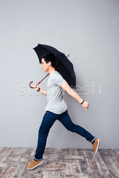 Stock photo: Man walking with umbrella in studio