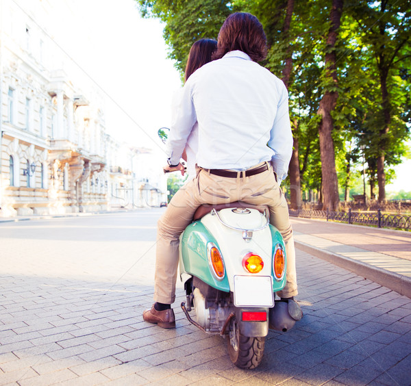 Back view protrait of a young couple on scooter Stock photo © deandrobot