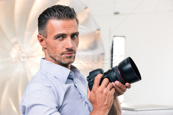Yakışıklı fotoğrafçı kamera portre bakıyor Stok fotoğraf © deandrobot