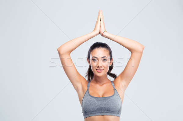 Fitness woman with joined hands over head Stock photo © deandrobot