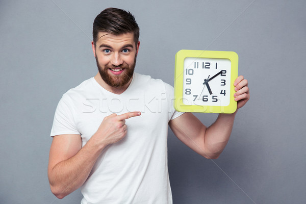 Casual man pointing finger on wall clock Stock photo © deandrobot
