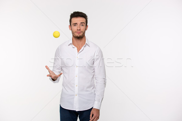 Handsome man throwing tennis ball Stock photo © deandrobot