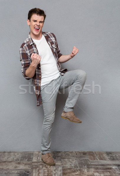 Delighted joyful young man dancing and smiling Stock photo © deandrobot