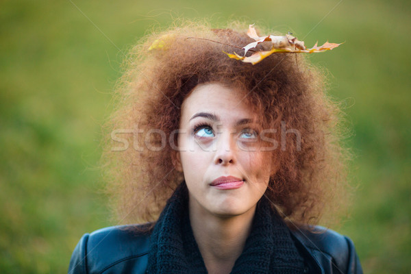 Woman looking up on leave in her curly hair Stock photo © deandrobot