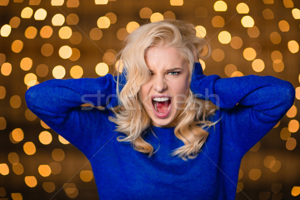 Blonde woman covering her ears and screaming Stock photo © deandrobot
