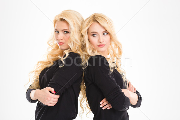 Serious sisters twins with arms folded Stock photo © deandrobot