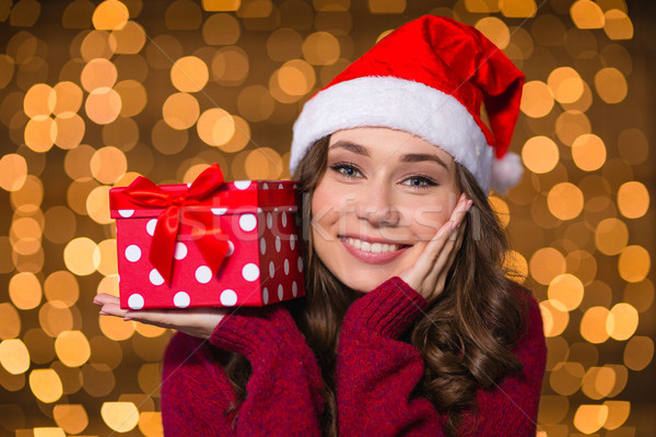 Dreaming smiling woman holding gift on palm over glittering background Stock photo © deandrobot