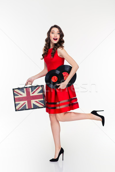 Happy curly woman running with vintage suitcase and vinyl disks Stock photo © deandrobot