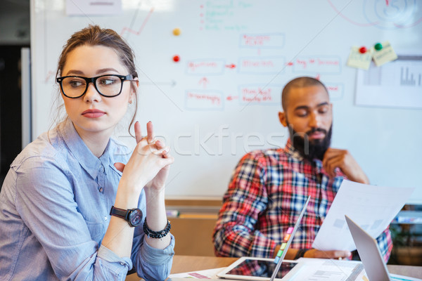 Pensive woman sitting and thinking while her male colleague reading  Stock photo © deandrobot