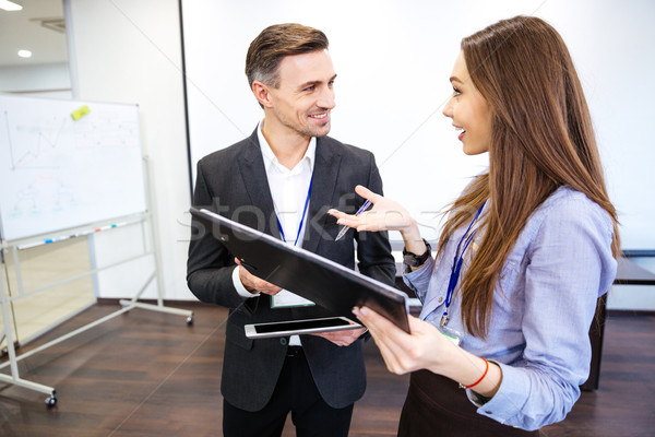 Two smiling businesspeople talking and working together Stock photo © deandrobot