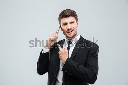 Smiling handsome young businessman gesturing and talking on cell phone   Stock photo © deandrobot