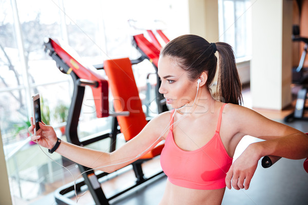Woman athlete taking selfie and listening to music in gym Stock photo © deandrobot