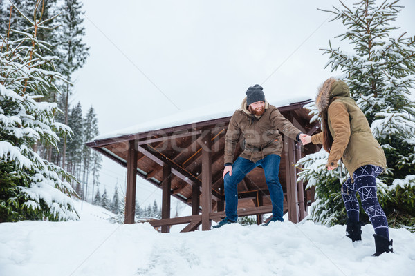 Man helping his girlfriend on walk mountains in winter Stock photo © deandrobot