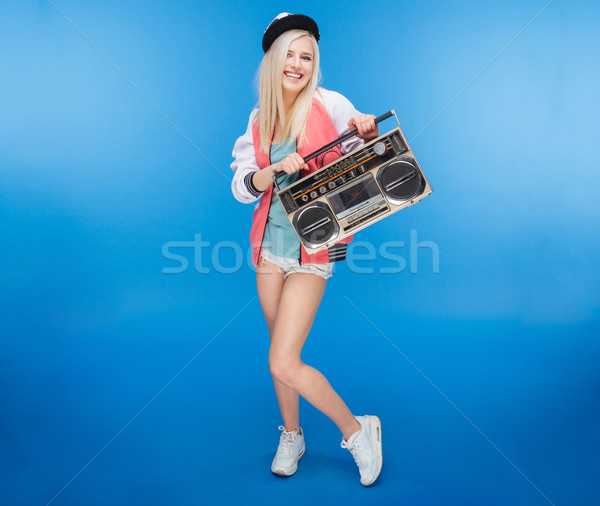 Smiling female teenager holding retro boom box  Stock photo © deandrobot