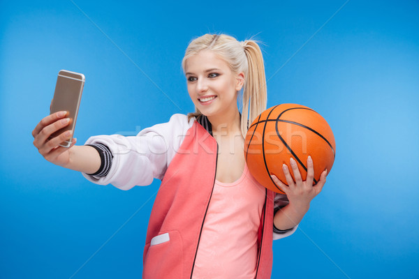 Female teenager holding basketball ball and making selfie photo Stock photo © deandrobot