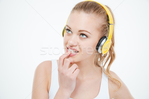 Pensive woman biting nails and listening to music in headphones  Stock photo © deandrobot