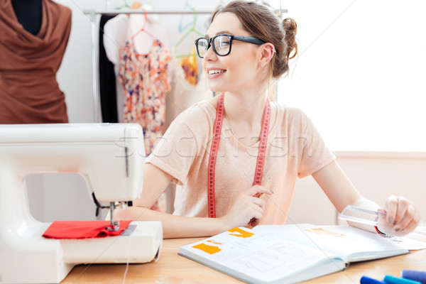 Smiling professional seamstress at work Stock photo © deandrobot