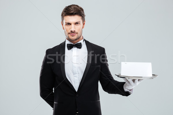 Butler in tuxedo and gloves holding tray with blank card Stock photo © deandrobot