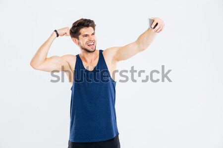 Cheerful young sportsman showing biceps and taking selfie with smartphone Stock photo © deandrobot