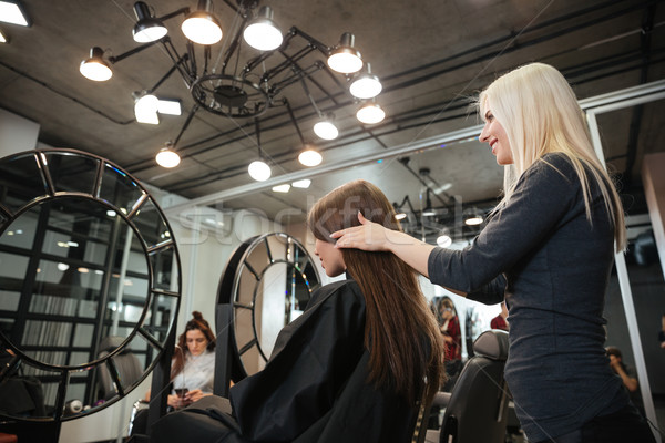 Female hairdresser making hairstyle to woman in salon Stock photo © deandrobot