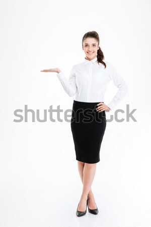 Stock photo: Cheerful businesswoman pointing finger away over white background
