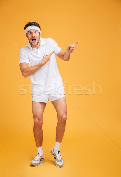 Wondered surprised young man athlete pointing away with both hands Stock photo © deandrobot