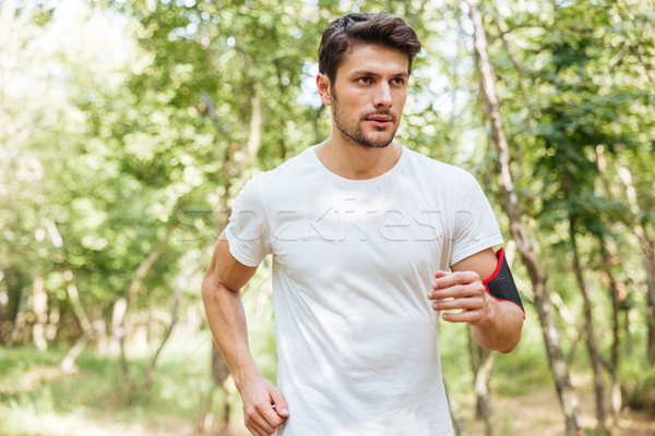 Sportsman with handband running in forest in the morning Stock photo © deandrobot