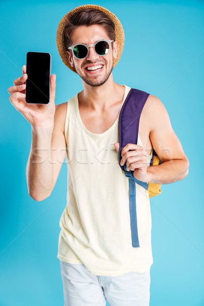 Happy young man with backpack showing blank screen mobile phone Stock photo © deandrobot