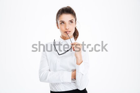 Thoughtful young business woman holding glasses and thinking Stock photo © deandrobot