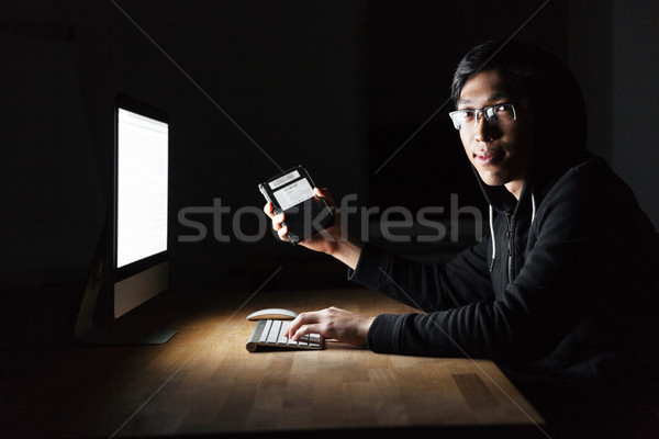 Hacker using computer and stealing information from hard disk Stock photo © deandrobot